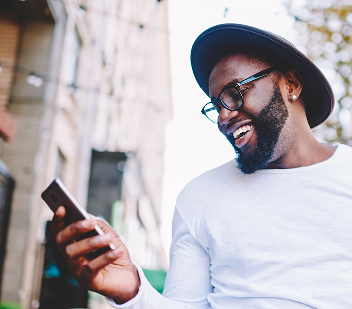 Man with hat, smiling and looking at phone.