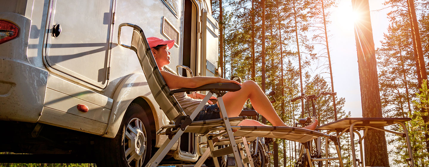 Woman enjoying sunshine in a chair beside her RV.