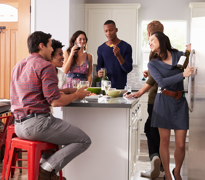 Group of friends stand around a kitchen island, eating & chatting.