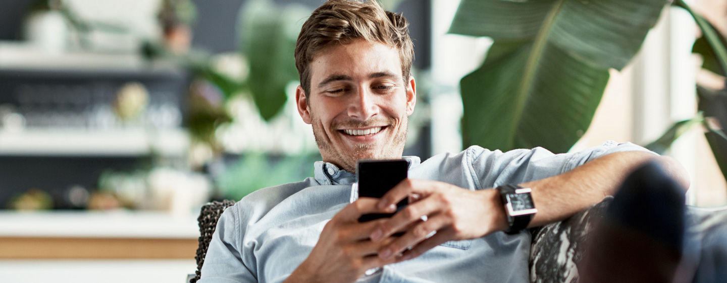 A man smiles as he uses his cellphone.