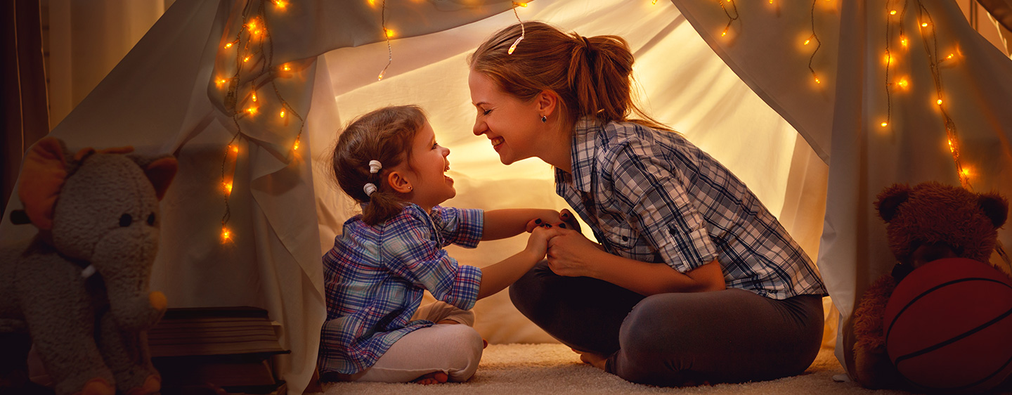Mom and daughter playing in a tent.