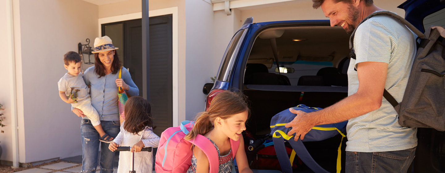 Family packing up a car with bags for a vacation.