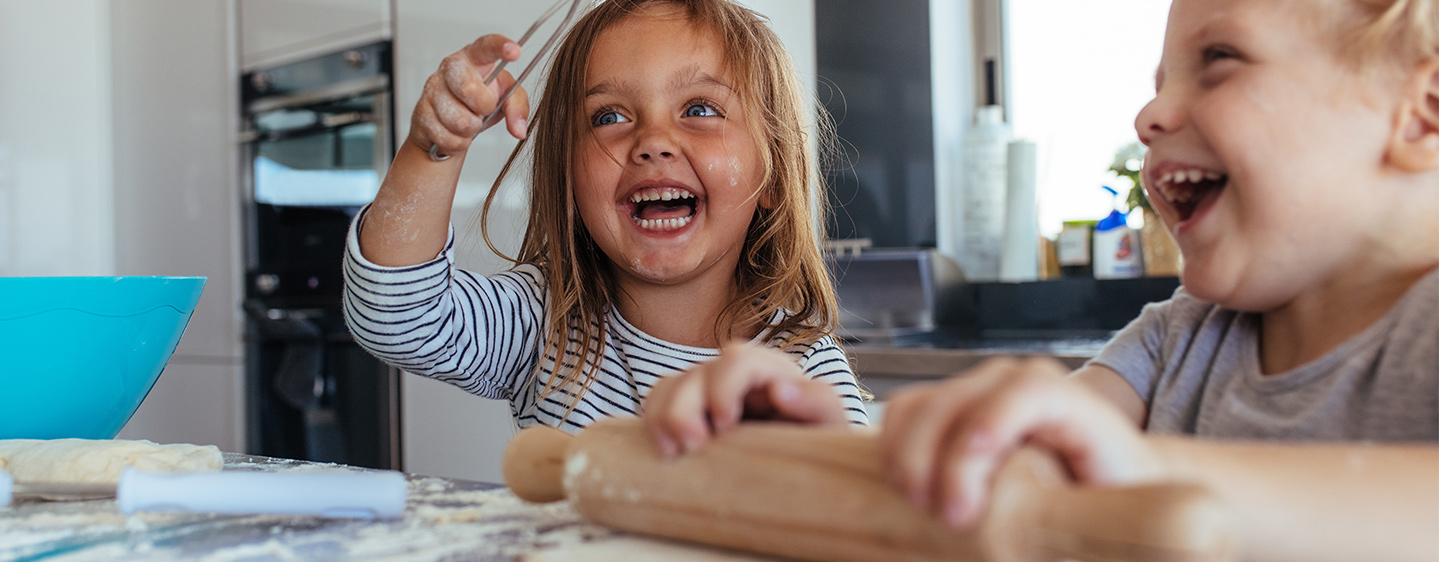 Little girl with big grin, baking with her brother and making a mess.