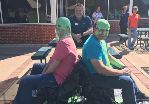 Two team members slimed in a fun challenge.