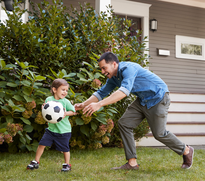 A dad and his son play in front of a home.
